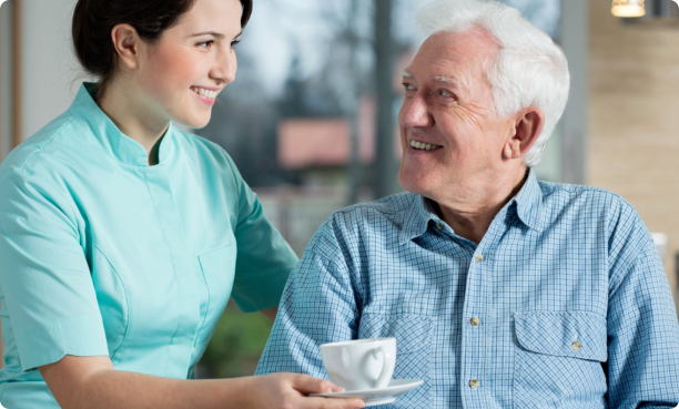 Caregiver giving coffee to old man